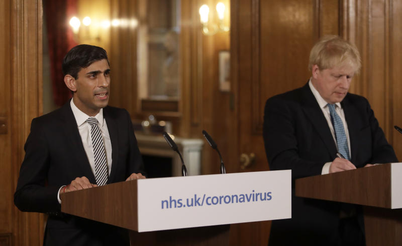 Britain's Chancellor Rishi Sunak, left, is flanked by British Prime Minister Boris Johnson as he gives a press conference inside 10 Downing Street in London, Tuesday, March 17, 2020 about the ongoing situation with the COVID-19 coronavirus outbreak. For most people, the new coronavirus causes only mild or moderate symptoms, such as fever and cough. For some, especially older adults and people with existing health problems, it can cause more severe illness, including pneumonia. (AP Photo/Matt Dunham, Pool)