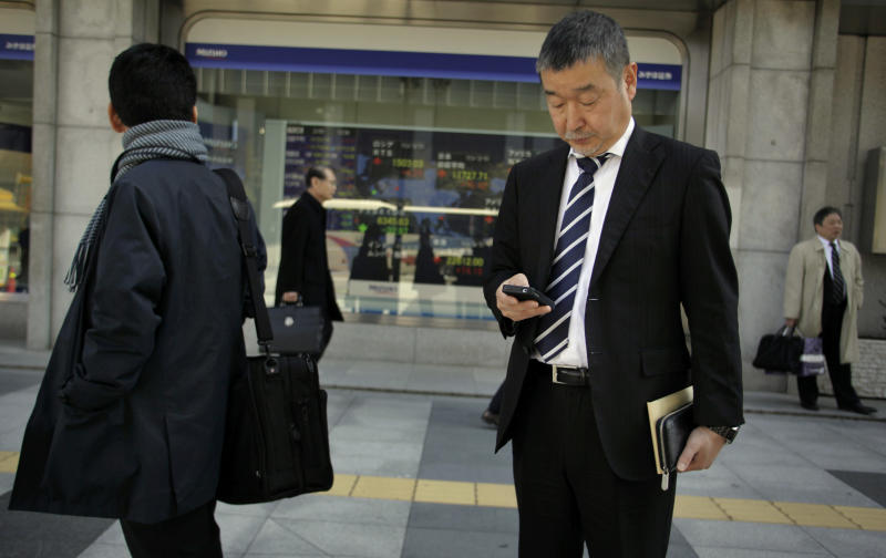 A man checks his cell phone outside a securities firm in Tokyo, Tuesday, March 5, 2013. Stocks in Tokyo rose on hopes that the Bank of Japan, which begins a two-day meeting on Wednesday, might demonstrate a shift in monetary policy to conform to the program championed by new Prime Minister Shinzo Abe. The Nikkei 225 index advanced 0.4 percent to 11,702.46. (AP Photo/Junji Kurokawa)