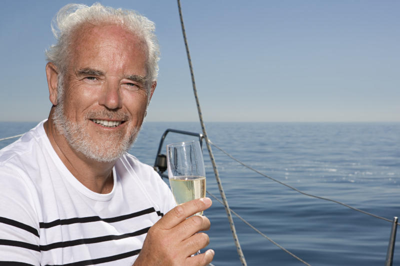 Older man out on the water holding a champagne glass
