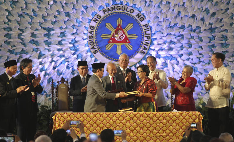 In this handout photo released by the Malacanang Photo Bureau, President Benigno S. Aquino III, third from right, Moro Islamic Liberation Front (MILF) Chairman, Al Haj Murad Ebrahim, third from left, Malaysian Prime Minister Najib Razak, center, and Secretary Teresita Quintos-Deles, Presidential Adviser on the Peace Process, second from right, applaud as they witness the exchange of the signed Comprehensive Agreement on the Bangsamoro (CAB) by MILF chief negotiator Mohagher Iqbal, fourth from left, and Miriam Coronel Ferrer, fourth from right, of the Philippine government in a ceremony at the Malacanang Presidential Palace in Manila, Philippines on Thursday March 27, 2014. The Philippine government signed a peace accord with the country's largest Muslim rebel group on Thursday, the culmination of years of negotiations and a significant political achievement for President Aquino.(AP Photo/Malacanang Photo Bureau, Ryan Lim)
