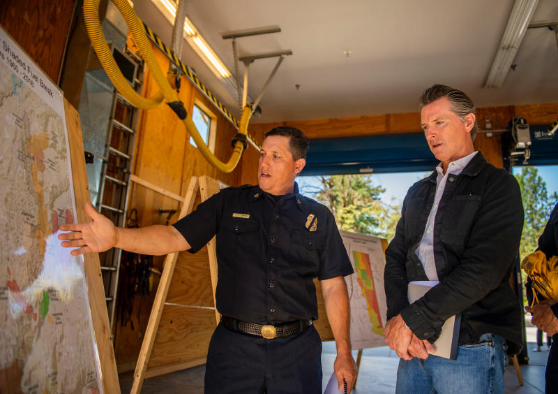 Gov. Gavin Newsom looks at a map with a Cal Fire personnel, Steve Garcia, that details the effort of the Emergency Wildfire Forest Management Project at the Colfax Fire House 30 in Colfax, Calif. Wednesday, July 31, 2019. (Daniel Kim/The Sacramento Bee via AP, Pool)