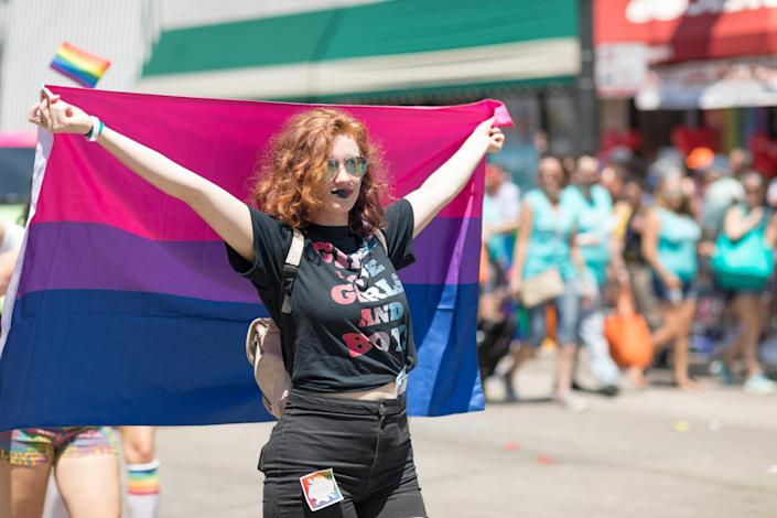 A woman is seen holding the bisexual pride flag at a recent Pride March in Chicago. (Photo: Getty Images)