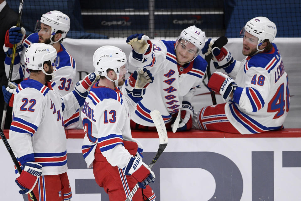 New York Rangers left wing Alexis Lafrenière (13) celebrates his goal with defenseman Anthony Bitetto (22), right wing Julien Gauthier (12) and left wing Brendan Lemieux (48) during the second period of an NHL hockey game against the Washington Capitals, Saturday, Feb. 20, 2021, in Washington. (AP Photo/Nick Wass)