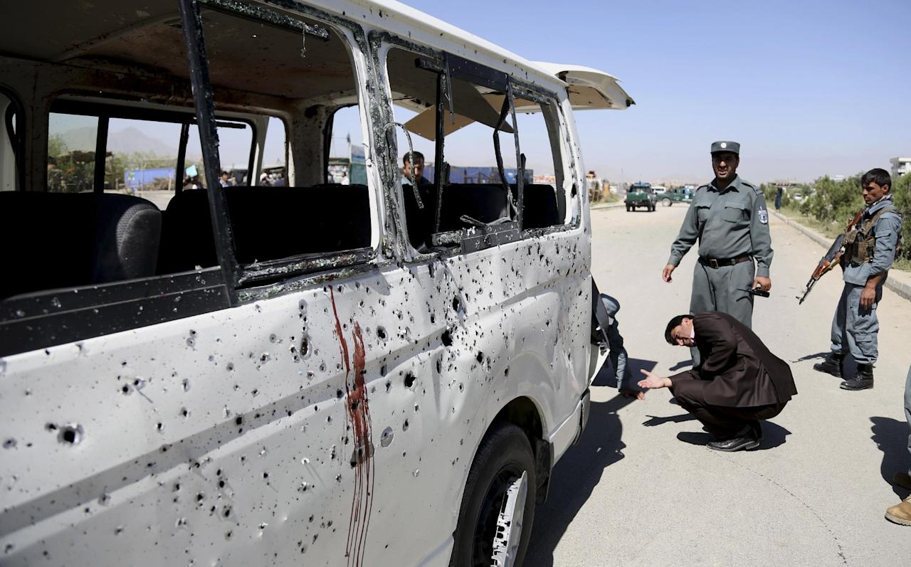 Afghan security personnel investigate a damaged vehicle after it was hit by a remote-controlled bomb on the outskirts of Kabul, Afghanistan, Tuesday, July 15, 2014. Gul Agha Hashimi, the chief of criminal investigations with the Kabul police, says the explosion struck a minivan carrying seven staffers of the palace's media office on Tuesday morning. The blast killed two passengers and also wounded five people, including the driver. (AP Photo/Rahmat Gul)
