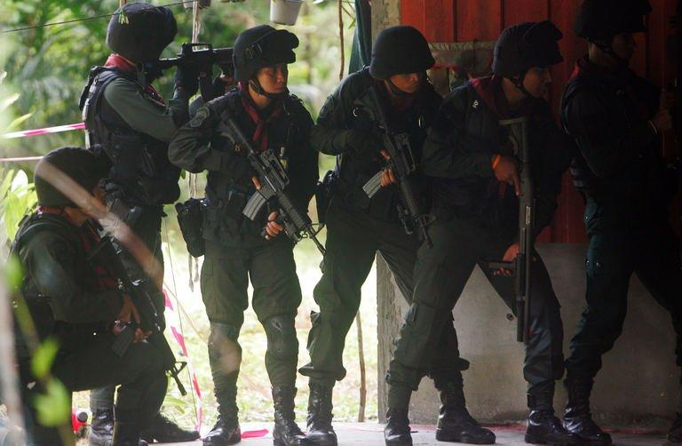 Thai police stand guard during an attack by suspected insurgents on a military base in Thailand's restive southern province of Narathiwat on February, 13, 2013. In the unusually brazen early-morning assault, 100 militants, dressed in army fatigues and armed with AK47 and M16 assault rifles, attacked the base