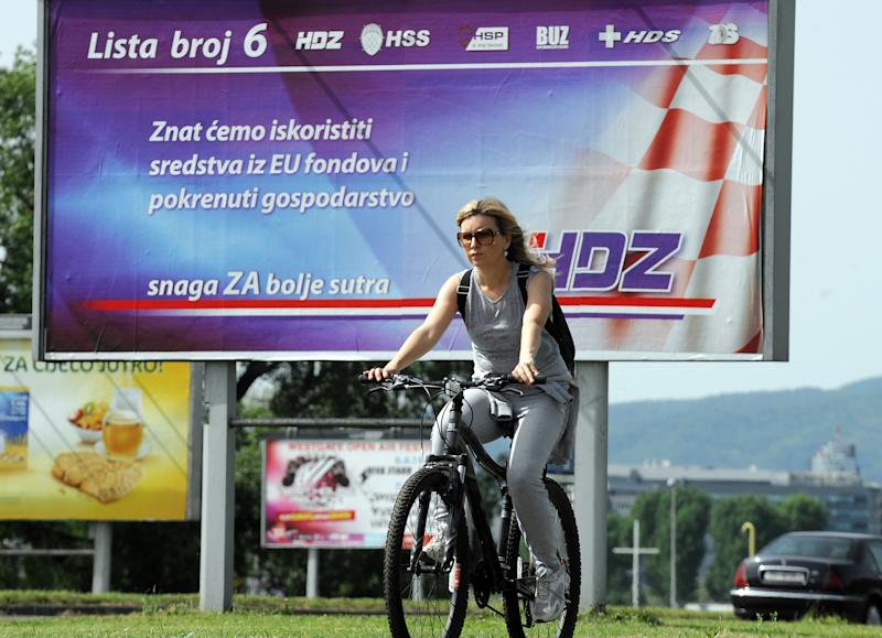 A woman cycles past a billboard for the Croatian Democratic Union (HDZ) and coalition partners in central Zagreb,Croatia, on May 23, 2014 ahead of elections to the European Parliament (AFP Photo/)