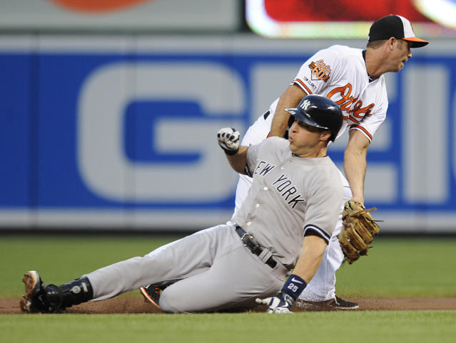 Baltimore Orioles shortstop J.J. Hardy, right, tags out New York Yankees Mark Teixeira, on a throw from Nick Markakis in the first inning of a baseball game, Sunday, July 13, 2014, in Baltimore.(AP Photo/Gail Burton)