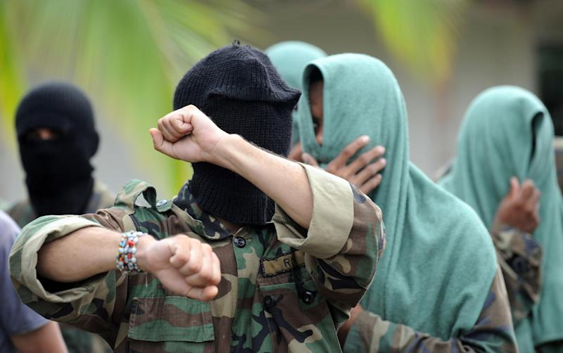 Members of a bandit group cover their faces as they surrender on May 21, 2009 in Uraba