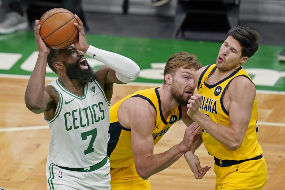 Boston Celtics guard Jaylen Brown (7) shoots against Indiana Pacers forward Domantas Sabonis, middle, and forward Doug McDermott, right, in the second half of an NBA basketball game, Friday, Feb. 26, 2021, in Boston. (AP Photo/Elise Amendola)