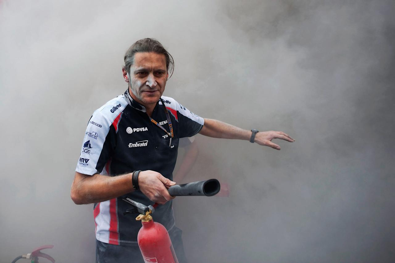 BARCELONA, SPAIN - MAY 13:  A Williams mechanic helps fight the fire that broke out at the back of their team garage after they celebrated winning the Spanish Formula One Grand Prix at the Circuit de Catalunya on May 13, 2012 in Barcelona, Spain.  (Photo by Peter J Fox/Getty Images)