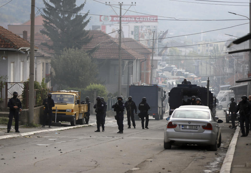 Kosovo police officers guard a street in the northern Serb-dominated part of ethnically divided town of Mitrovica, Kosovo, Wednesday, Oct. 13, 2021. Kosovo police have clashed with ethnic Serbs in the north during an operation against smuggling of goods. A police statement said that an operation against smuggled goods was held in four areas, including northern Mitrovica which is mostly populated by ethnic Serbs. (AP Photo/Bojan Slavkovic)