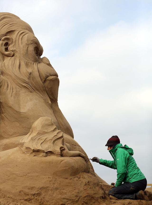 WESTON-SUPER-MARE, ENGLAND - MARCH 26: Sand sculptor Helena Bangert, from Holland works on a sand sculpture of King Kong as pieces are prepared as part of this year's Hollywood themed annual Weston-super-Mare Sand Sculpture festival on March 26, 2013 in Weston-Super-Mare, England. Due to open on Good Friday, currently twenty award winning sand sculptors from across the globe are working to create sand sculptures including Harry Potter, Marilyn Monroe and characters from the Star Wars films as part of the town's very own movie themed festival on the beach. (Photo by Matt Cardy/Getty Images)