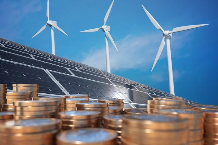 Stacks of coins with wind turbines and solar panels in the background