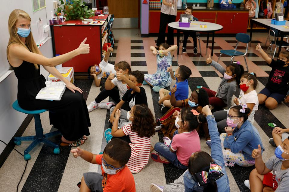 A teacher seated at the front of a classroom gives the thumbs-up sign to a dozen and a half elementary students seated on the floor.