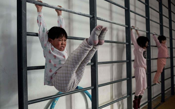 Some Chinese gymnasts train relentlessly from as young as four in the pursuit of gold medals - NICOLAS ASFOURI/AFP