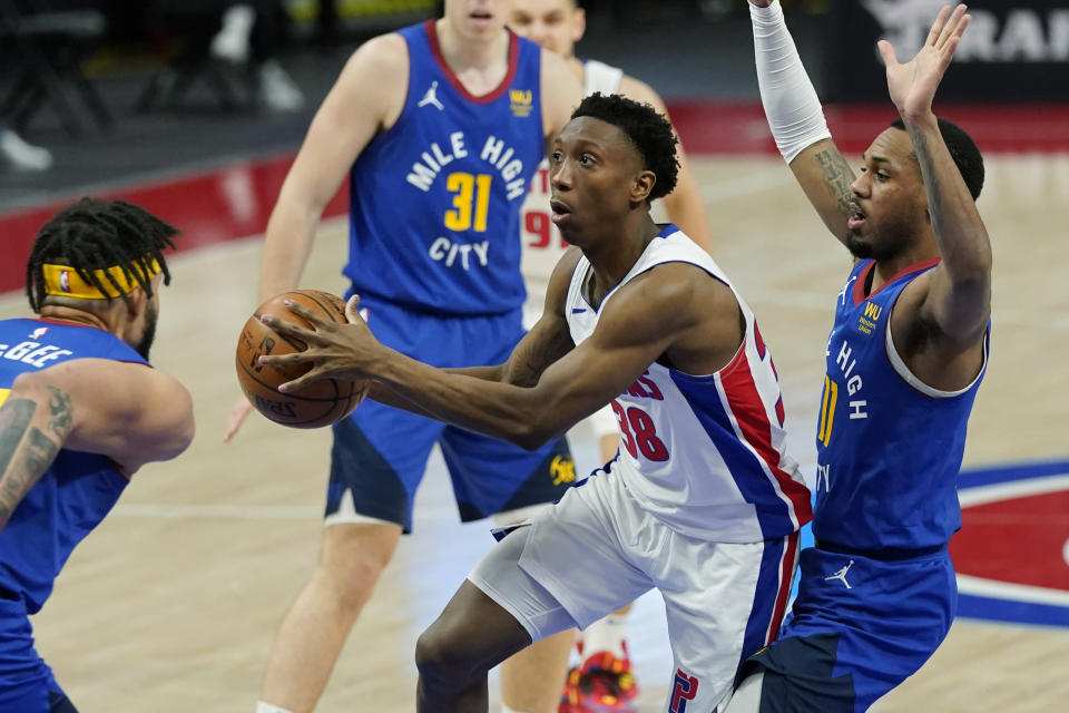 Detroit Pistons guard Saben Lee (38) passes as Denver Nuggets center JaVale McGee, left, defends during the second half of an NBA basketball game, Friday, May 14, 2021, in Detroit. (AP Photo/Carlos Osorio)