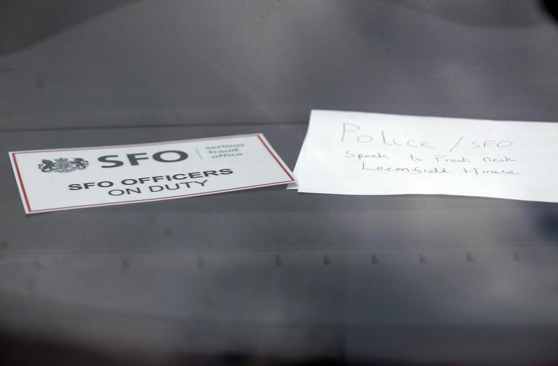 A sign is displayed in an unmarked Serious Fraud Office vehicle parked outside a building, in Mayfair, central London