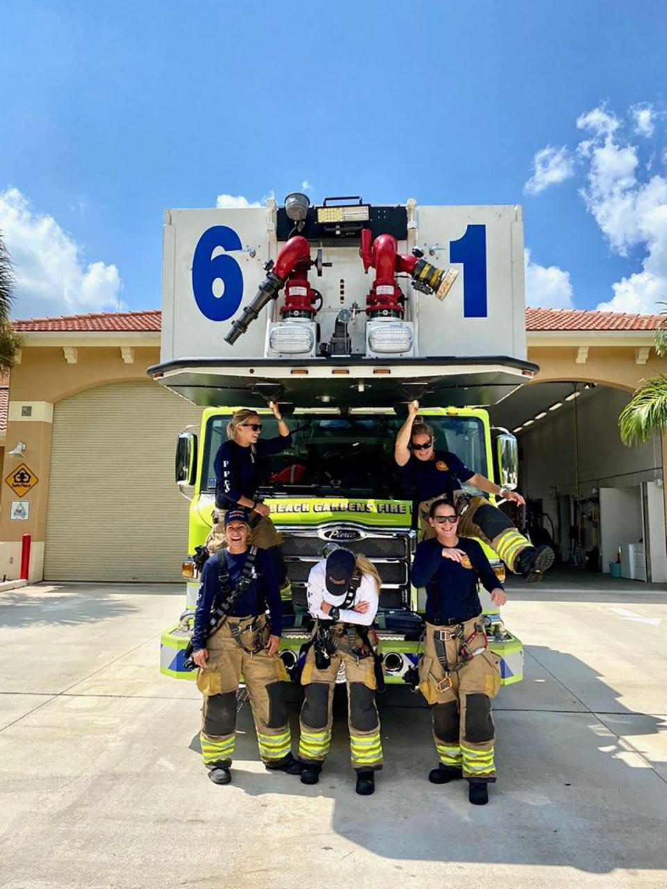 In this September 2020 photo provided by Palm Beach Gardens Fire and Rescue, firefighters lieutenant Kelsey Krzywada and Driver Engineer Sandi Ladewski (Sitting opposite on the truck), Lieutenant Krystyna Krakowski, fire medic Julie Dudley and Lieutenant (Acting Captain) Monica Marzullo (standing in front of the truck) pose at their station in Palm Beach Gardens, Fla. (Kodi Cabral/Courtesy of Palm Beach Gardens Fire and Rescue via AP)