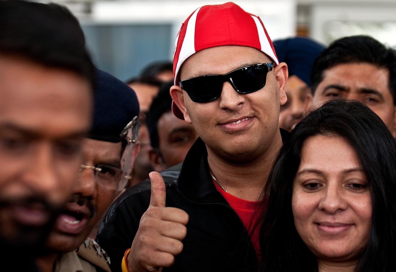 Indian cricketer Yuvraj Singh (C) gestures upon his arrival at Indira Gandhi International Airport in New Delhi on April 9, 2012. India's World Cup cricket hero Yuvraj Singh has returned home after receiving treatment for a cancerous tumour in the United States.Sporting a black jacket and red baseball cap, the 30-year-old all-rounder gave thumbs up signs to well-wishers who had gathered at New Delhi airport to welcome him back.     AFP PHOTO/ MANAN VATSYAYANA (Photo credit should read MANAN VATSYAYANA/AFP/Getty Images)