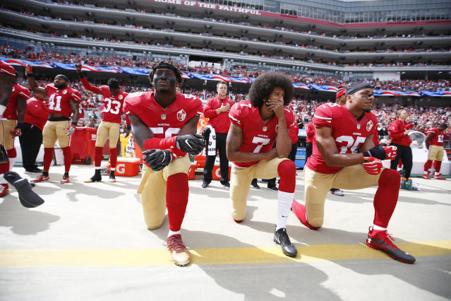 Antoine Bethea and Rashard Robinson raise their fists during the national anthem as Eli Harold, left, Colin Kaepernick and Eric Reid take a knee prior to a game against the Dallas Cowboys on Oct. 2, 2016. (Michael Zagaris/San Francisco 49ers via Getty Images)