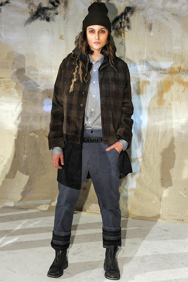 <p>A model in a black beanie, plaid coat, and navy shirt and trousers at the Krammer and Stoudt runway show (Photo: Getty Images) </p>
