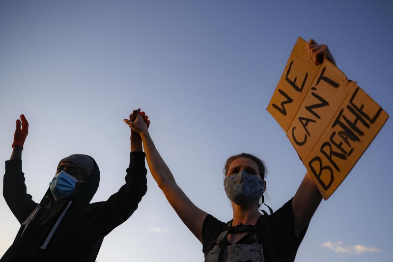 "Protestors demonstrate on University Avenue while holding a ""WE CAN'T BREATHE"" sign and wearing protective masks, Thursday, May 28, 2020, in St. Paul, Minn. Protests over the death of George Floyd, a black man who died in police custody Monday, broke out in Minneapolis for a third straight night. (AP Photo/John Minchillo)"