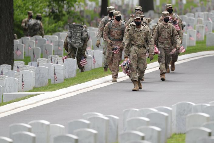 U.S. Army soldiers honoring service members who are buried at Arlington National Cemetery in Virginia. (Tom Brenner/Reuters)