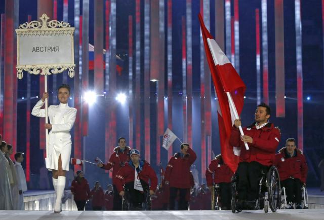 Austria's flag-bearer Philipp Bonadimann (R), leads his country's contingent during the opening ceremony of the 2014 Paralympic Winter Games in Sochi, March 7, 2014. REUTERS/Alexander Demianchuk (RUSSIA - Tags: OLYMPICS SPORT)