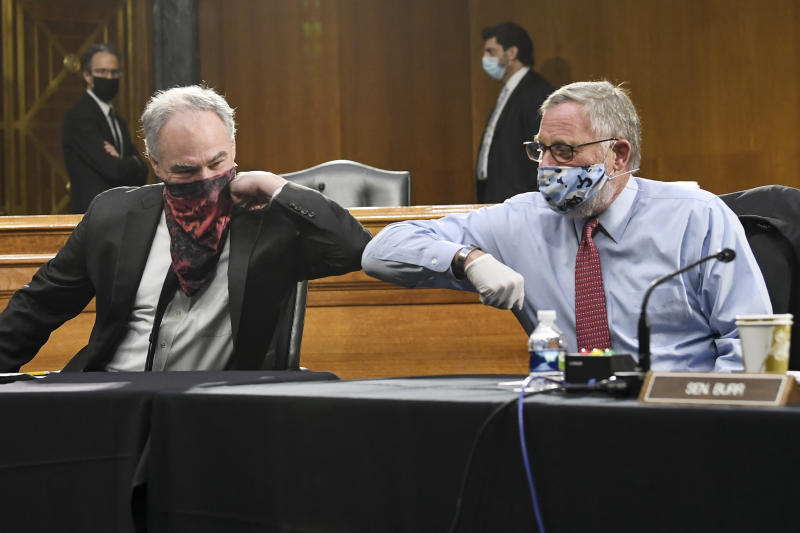 Sen. Tim Kaine, D-Va., left, and Sen. Richard Burr, R-N.C., greet each other with an elbow bump before the Senate Committee for Health, Education, Labor, and Pensions hearing, Tuesday, May 12, 2020 on Capitol Hill in Washington. Dr. Anthony Fauci, director of the National Institute of Allergy and Infectious Diseases, is to testify before the committee.  (Toni L. Sandys/The Washington Post via AP, Pool)