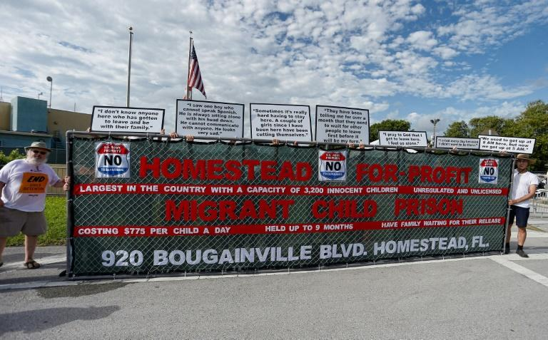 Activists hold a sign in front of a detention center in Homestead, Florida where migrant children who have been separated from their families are being held (AFP Photo/RHONA WISE)