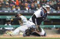 Pittsburgh Pirates' Gregory Polanco beats the throw to Detroit Tigers catcher James McCann to score on an RBI single by teammate Corey Dickerson during the fourth inning of a baseball game, Friday, March 30, 2018, in Detroit. (AP Photo/Carlos Osorio)