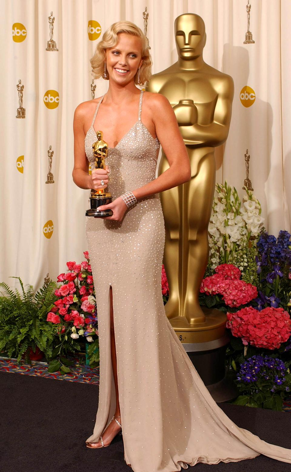 """<p>Theron was Hollywood's golden girl when she took home the Oscar for her transformative performance in """"Monster."""" The actress' champagne-coloured gown by Tom Ford was one of the designer's last looks for Gucci, before launching his own fashion house the following year.</p>"""