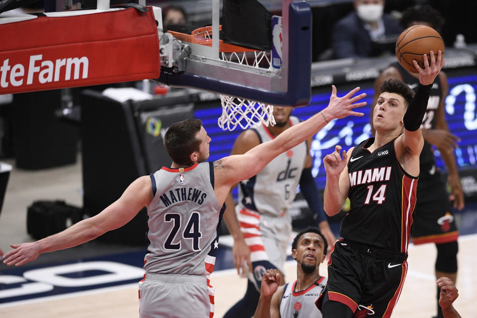 Miami Heat guard Tyler Herro (14) goes to the basket against Washington Wizards guard Garrison Mathews (24) during the second half of an NBA basketball game, Saturday, Jan. 9, 2021, in Washington. (AP Photo/Nick Wass)