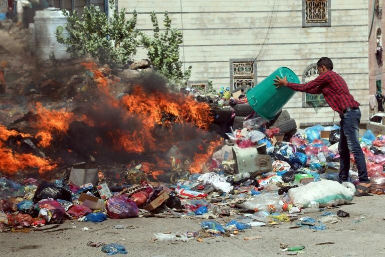 A man disposes of rubbish at a garbage dump on a main street in the third-largest city Taez in southwestern Yemen