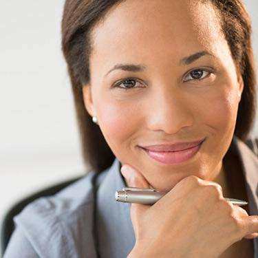 Confident--businesswoman-smiling-with-hand-on-chin_web