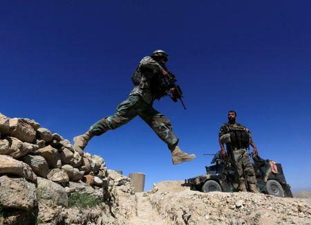 A member of Afghanistan's Special Forces unit jumps from a wall during patrol in Pandola village near the site of a U.S. bombing in the Achin district of Nangarhar