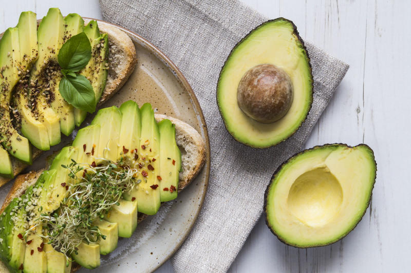 Sliced avocados on a plate, adorned with chill flakes, salt and herbs.