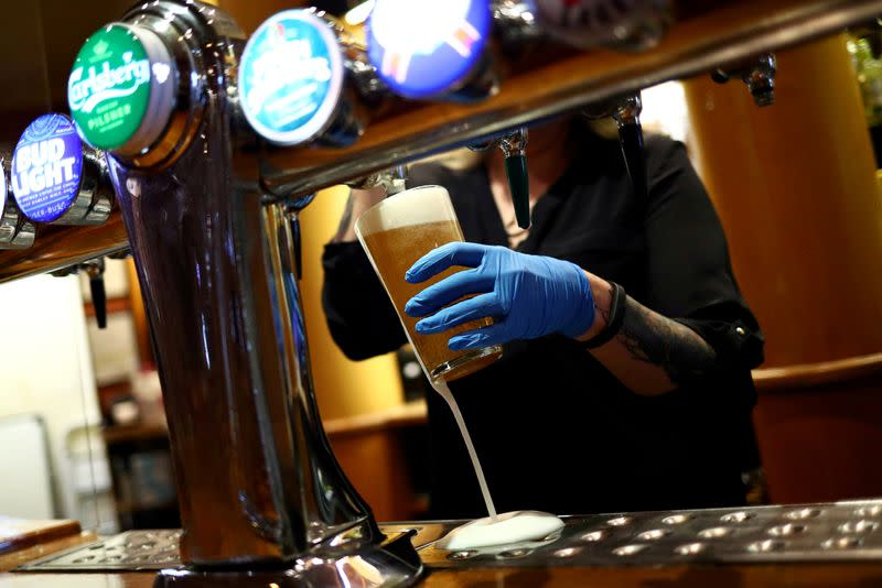 FILE PHOTO: A worker serves a beer at The Holland Tringham Wetherspoons pub in London