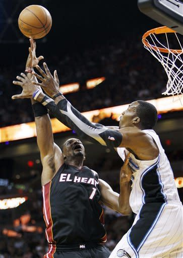 Miami Heat's Chris Bosh (1) shoots as Orlando Magic's Dwight Howard, right, defends during the first half of an NBA basketball game, Sunday, March 18, 2012, in Miami. (AP Photo/Lynne Sladky)