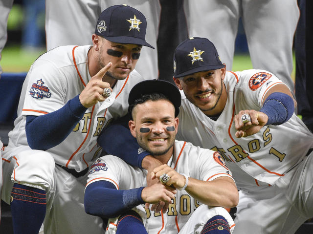 Houston Astros' Alex Bregman, left, Jose Altuve, center, and Carlos Correa show their World Series rings before the team's baseball game against the Baltimore Orioles, Tuesday, April 3, 2018, in Houston. (AP Photo/Eric Christian Smith)