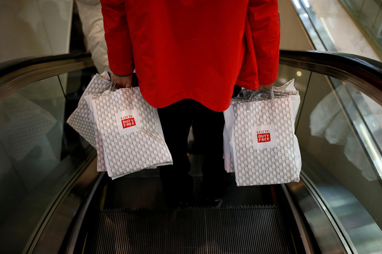 FILE PHOTO: A man carryng his shopping bags rides on an escalator at a Lotte duty free shop in Seoul, South Korea, December 13, 2016.   REUTERS/Kim Hong-Ji/File Photo                    GLOBAL BUSINESS WEEK AHEAD - SEARCH GLOBAL BUSINESS 27 MAR FOR ALL IMAGES