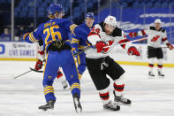 Buffalo Sabres defenseman Rasmus Dahlin (26) and New Jersey Devils forward Miles Wood (44) collide during the first period of an NHL hockey game Saturday, Jan. 30, 2021, in Buffalo, N.Y. (AP Photo/Jeffrey T. Barnes)