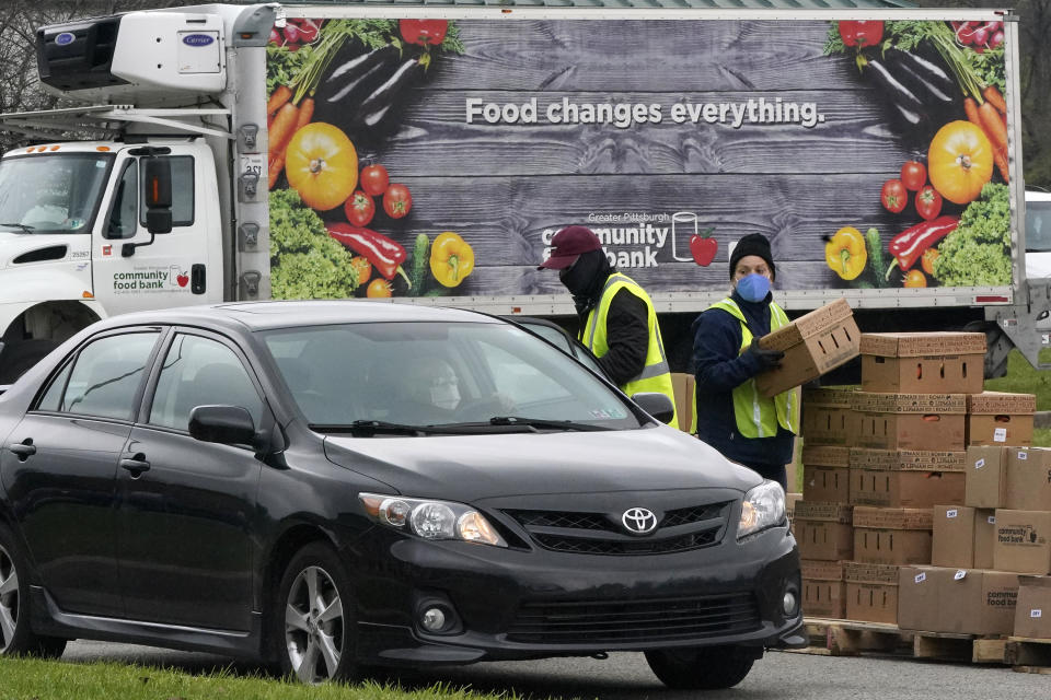 Volunteers load boxes of food into a car during a Greater Pittsburgh Community Food bank drive-up food distribution in Duquesne, Pa., Monday, Nov. 23, 2020. (AP Photo/Gene J. Puskar)