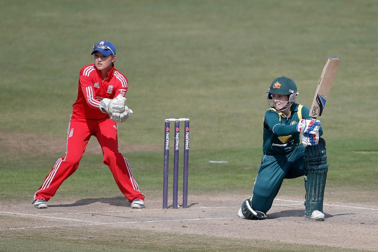 HOVE, ENGLAND - AUGUST 25: Jodie Fields of Australia hits out as England wicketkeeper Sarah Taylor looks on during the third NatWest One Day International match between England and Australia at the BrightonandHoveJobs.com County Ground on August 25, 2013 in Hove, England.  (Photo by Harry Engels/Getty Images)