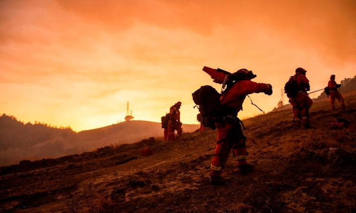 """<span class=""""element-image__caption"""">A crew of incarcerated firefighters make their way to firefighting operations to battle the Kincade fire in Healdsburg, California, last year.</span> <span class=""""element-image__credit"""">Photograph: Philip Pacheco/AFP via Getty Images</span>"""