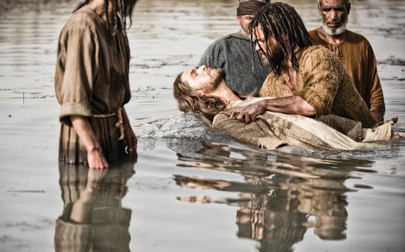 "This publicity image released by History shows Diogo Morcaldo as Jesus, center, being baptized by Daniel Percival, as John, in a scene from ""The Bible,"" premiering Sunday, March 3 at 8 p.m. EST on History. (AP Photo/History, Joe Alblas)"