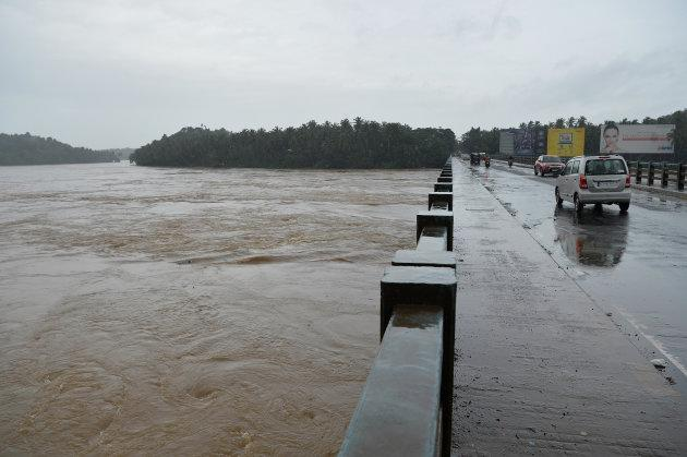 Vehicles drive on a bridge over the overflowing Chaliyar river in Kozhikode, Kerala, on 17 August.