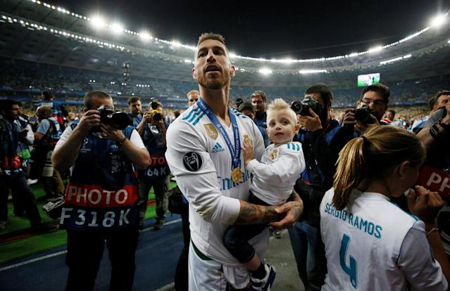 Soccer Football - Champions League Final - Real Madrid v Liverpool - NSC Olympic Stadium, Kiev, Ukraine - May 26, 2018 Real Madrid's Sergio Ramos celebrates with a child after winning the Champions League REUTERS/Gleb Garanich