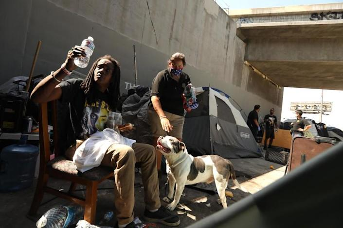 "Los Angeles Homeless Services Authority outreach worker Monica Palma, center, visits with Kim M. and her dog Dee-O-G who live homeless under the Santa Monica Freeway along Venice Boulevard in Los Angeles on July 8. <span class=""copyright"">(Genaro Molina / Los Angeles Times)</span>"