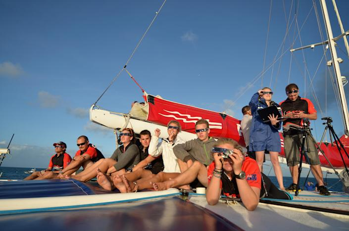 In this photo released by Tourism Queensland, people prepare to view a total solar eclipse while on a tour boat at Michelmas Cay on the Great Barrier Reef in Queensland state, Australia, Wednesday, Nov. 14, 2012. Starting just after dawn, the eclipse cast its 150-kilometer (95-mile) shadow in Australia's Northern Territory, crossed the northeast tip of the country and was swooping east across the South Pacific, where no islands are in its direct path. (AP Photo/Tourism Queensland, Ben Southall) EDITORIAL USE ONLY